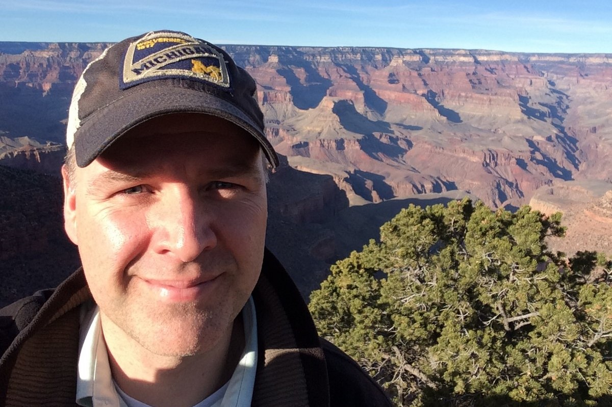 Jason Taylor, a middle aged man in a baseball cap, smiles in front of a canyon.