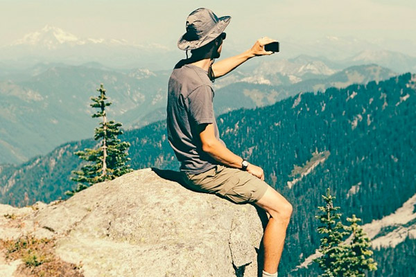 man sitting on cliff with mobile device